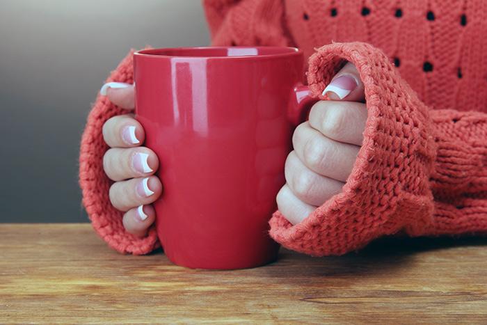 греет руки об чашку